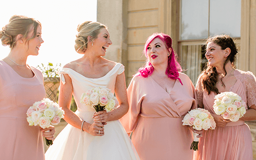 Bride and bridesmaids laughing and posing for a picture at Cliveden House