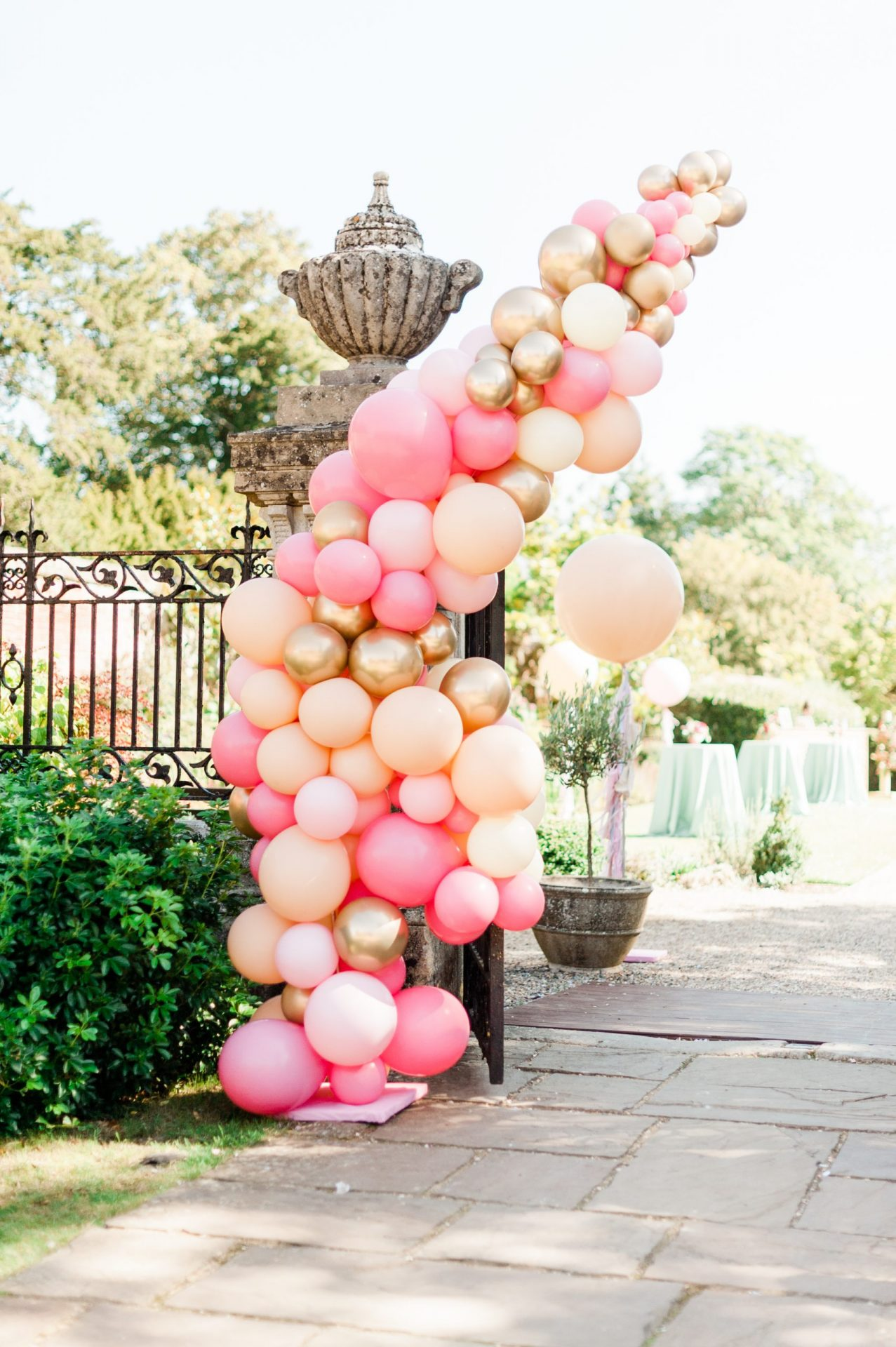 Half balloon arch at a gate entrance in pinks, beige and gold colours