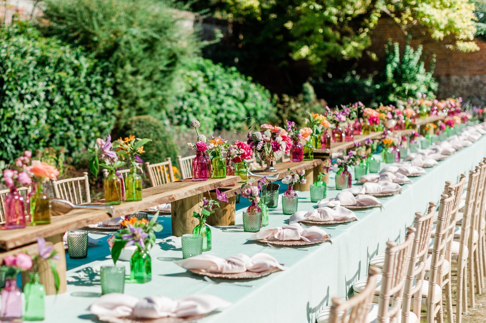 Long outdoor dinner table at Four Seasons Hampshire filled with colourful blooms