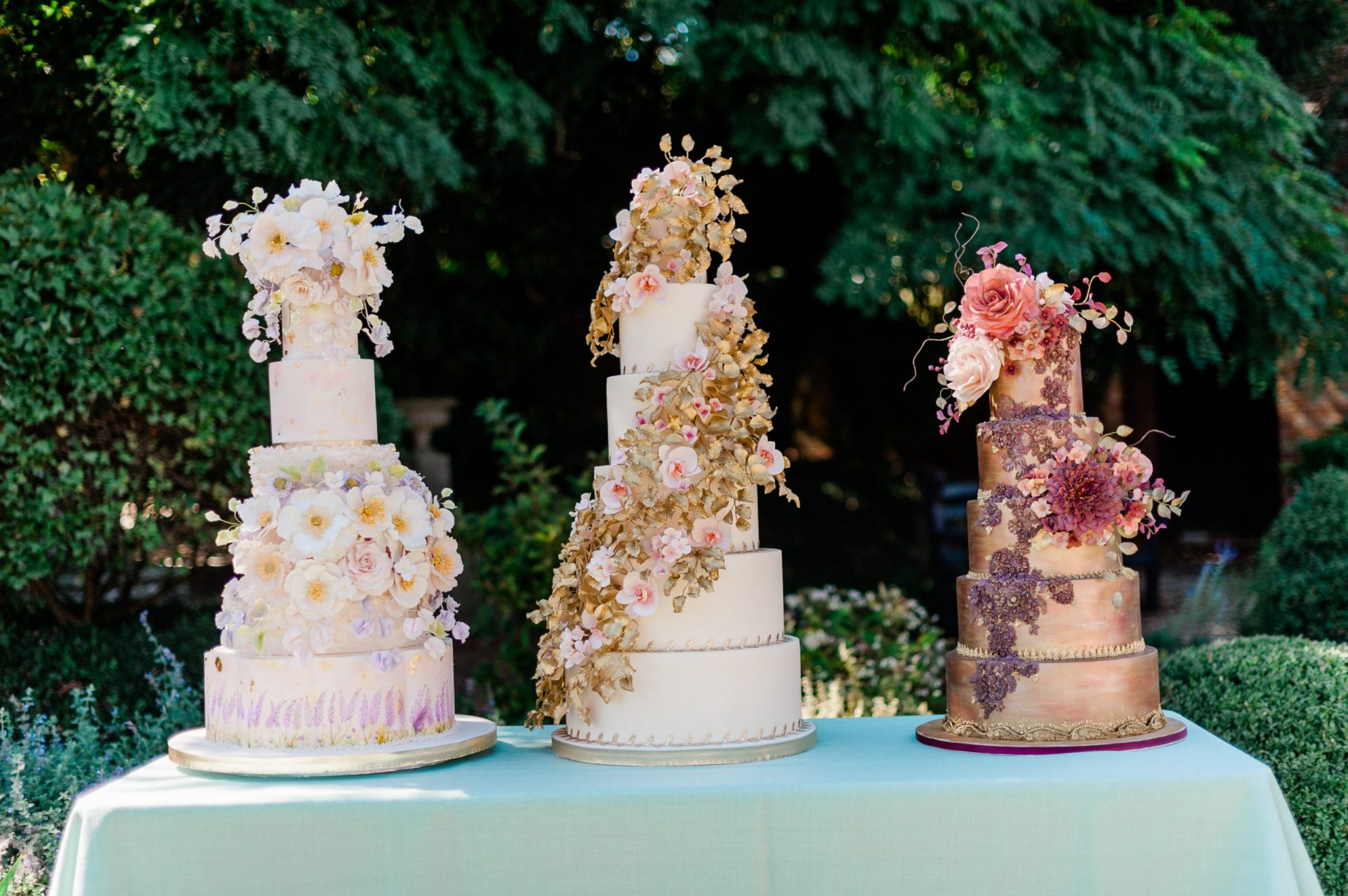 Three tiered wedding cakes by Unique Cakes by Yevnig on a turquoise table