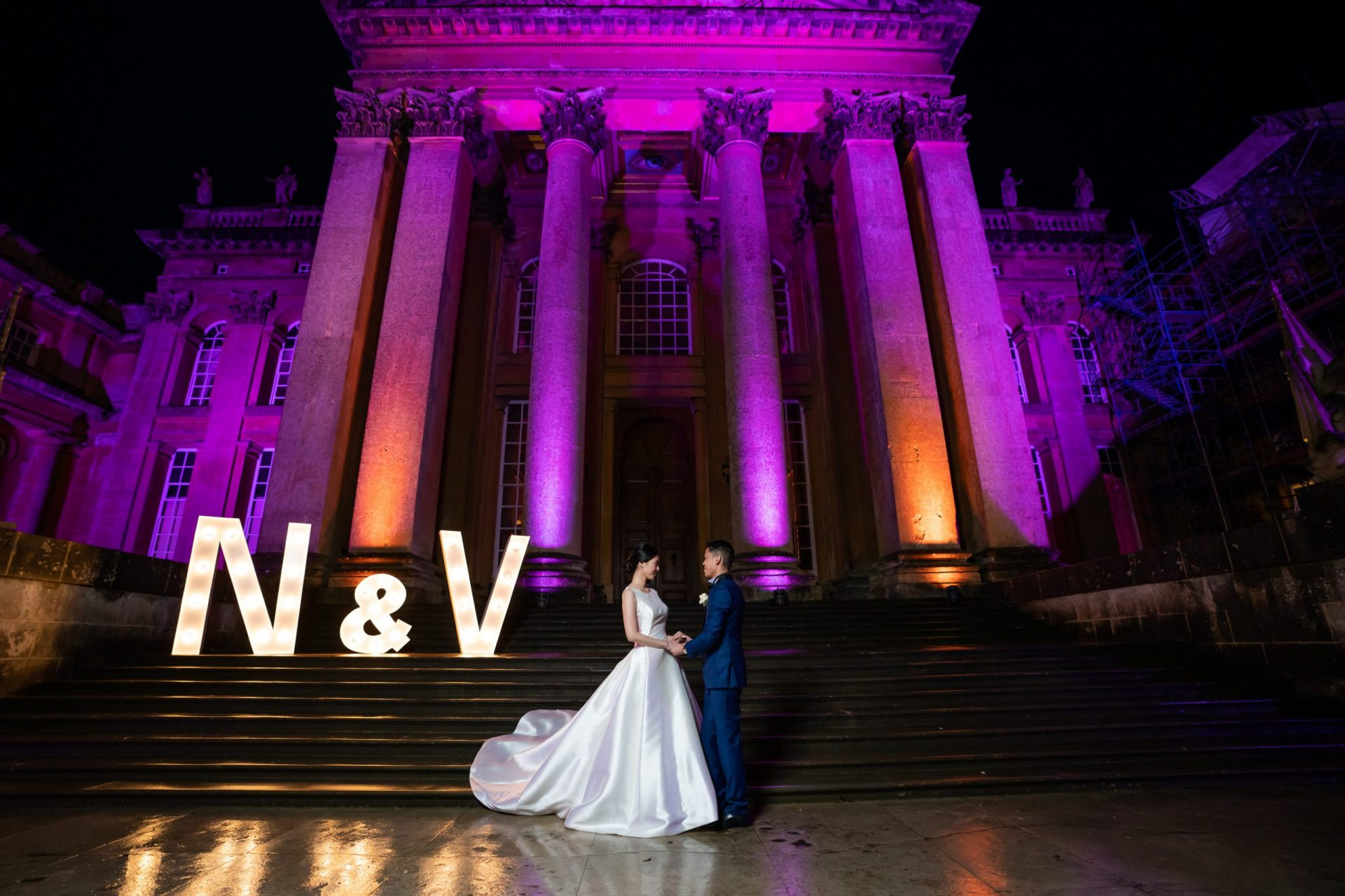Bride and groom standing in front of Blenheim Palace lit up in purple