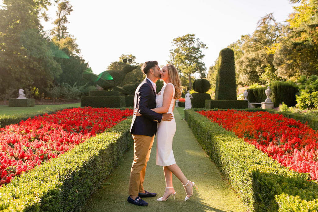 Bride and groom during their engagement shoot in a garden of red flowers at Cliveden House Hotel